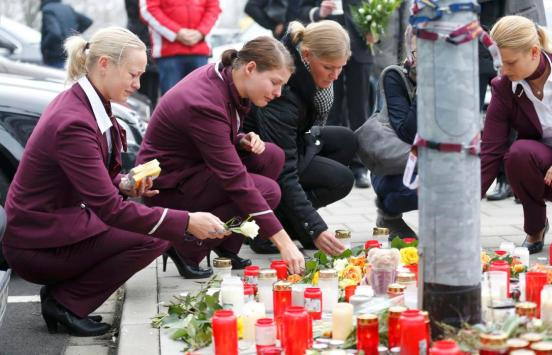 Germanwings employees cry as they place flowers and lit candles outside the company headquarters in Cologne Bonn airport